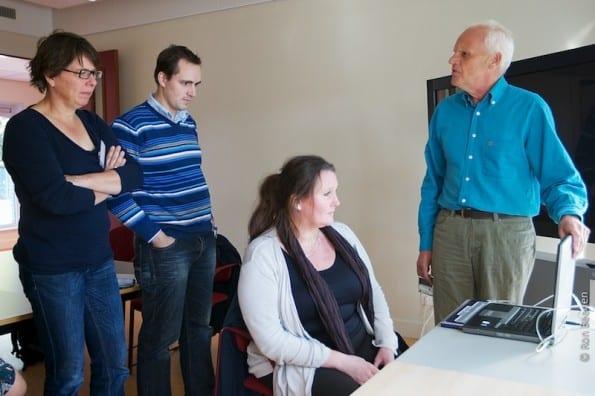 De visueel gehandicapte workshopleider legt uit aan enkele deelnemers hoe een screenreader werkt