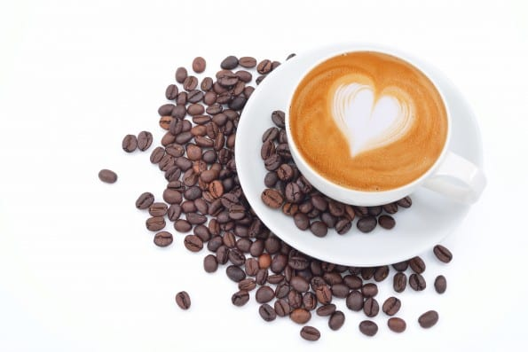 A cup of cafe latte and coffee beans on white