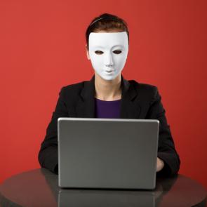 vrouw met masker achter laptop