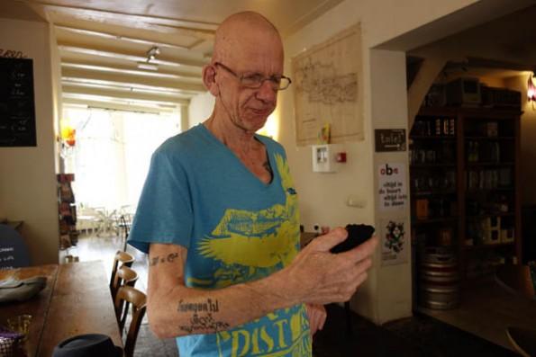 Eli Witteman, de kok van Hofje van Wijs in Amsterdam checkt of zijn salaris in Bitcoin al binnen is. Zijn tatoeage luidt: Thailand Forever. Foto Peter de Ruiter