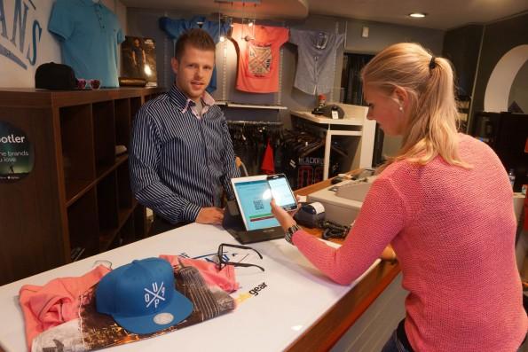 Een klant rekent af met DigiBytes bij Michael Hauser van House of Jeans in Zoetermeer. Met de 'wallet' op haar telefoon scant ze de QR-code op de tablet van de winkel. Ze drukt op OK: klaar! De toonbank herkent automatisch de goederen die er op liggen. Foto: Peter de Ruiter