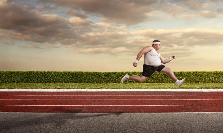 39373622 - funny overweight man speeding on the running track with copy space