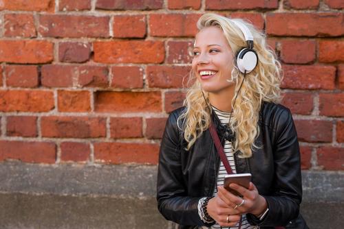 Vrolijke vrouw luistert naar muziek op telefoon