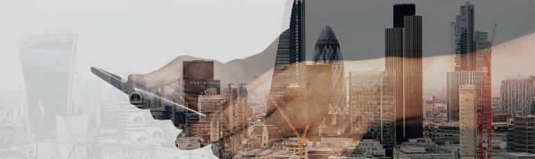 Afbeelding van de stad van de toekomst met daar overheen een persoon die een telefoon vasthoudt.