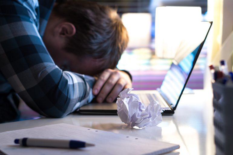 Schrijven writers block man met hoofd op laptop
