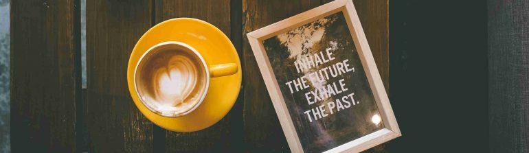 Afbeelding van een kop koffie met een notitie: Inhale the future, exhale the past.