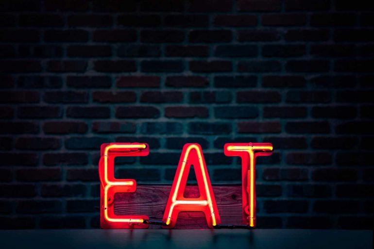 Eat logo voor een donkere muur.