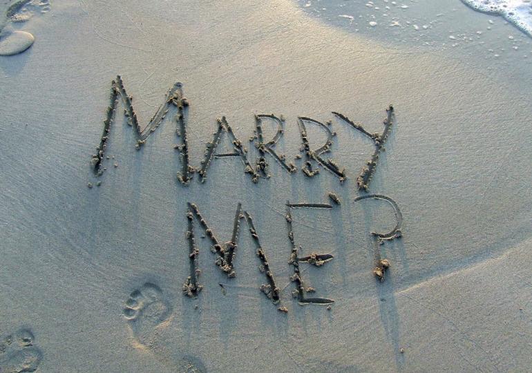 Foto van de geschreven tekst 'marry me?' in het zand.