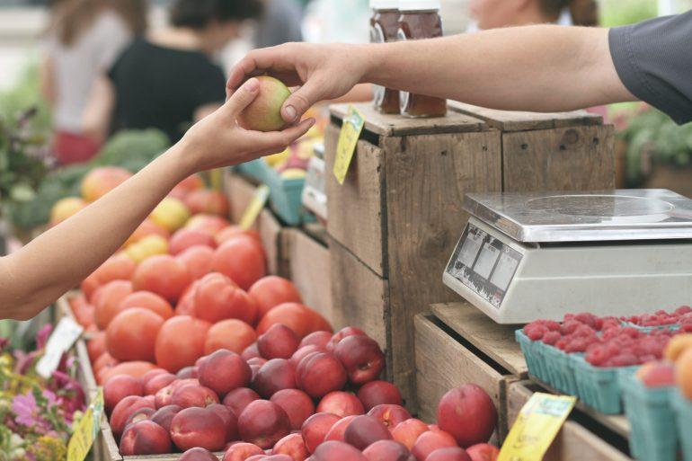 Foto van een marktkoopman die een appel geeft aan een klant. Een voorbeeld van een klantgerichte organisatie.
