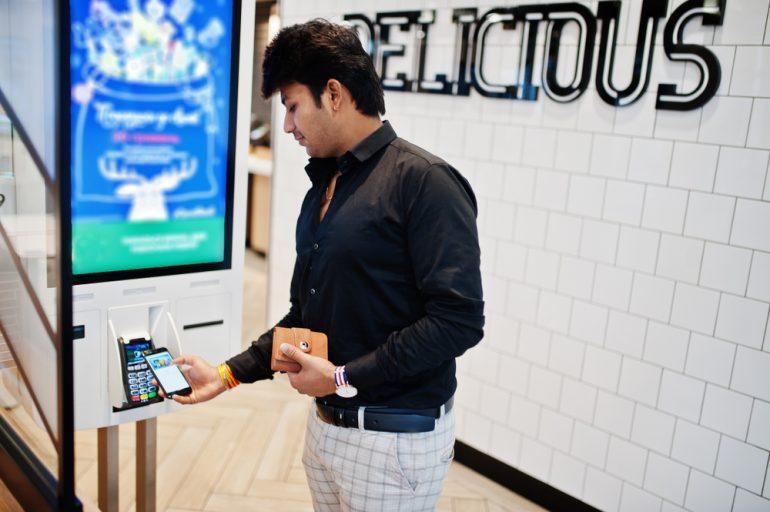Afbeelding van een persoon die met zijn telefoon afrekent.