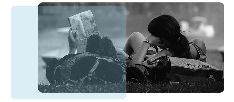 Afbeelding van twee personen die in het gras liggen en aan het lezen zijn.