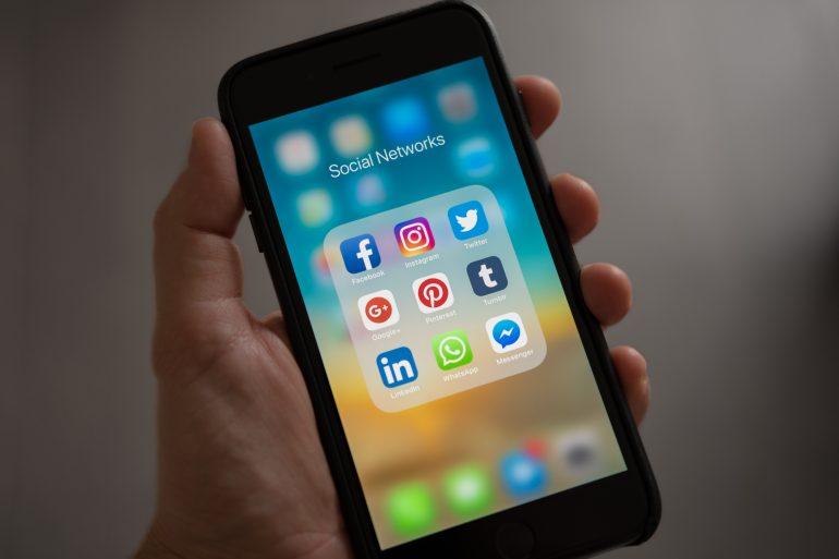 Foto van smartphone met social-media-icoontjes erop