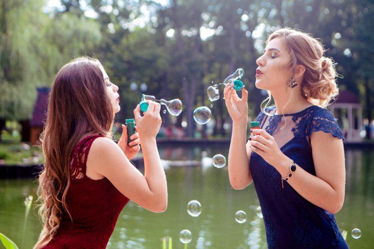 Foto van twee vrouwen die bellen blazen naar elkaar
