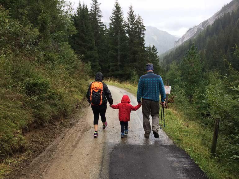 Vader wandelt met kinderen in de regen.