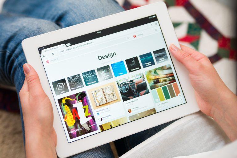 Iemand die op de tablet kijkt naar design op Pinterest.