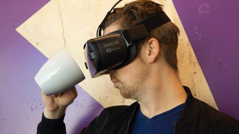 Foto van man met VR-bril die in een koffiemok kijkt