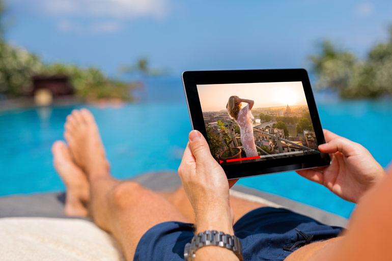 Man ligt aan het zwembad, kijkt Netflix op tablet.