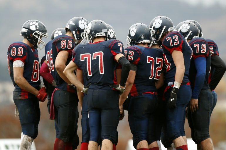 Foto van American football-spelers in overleg (een huddle)