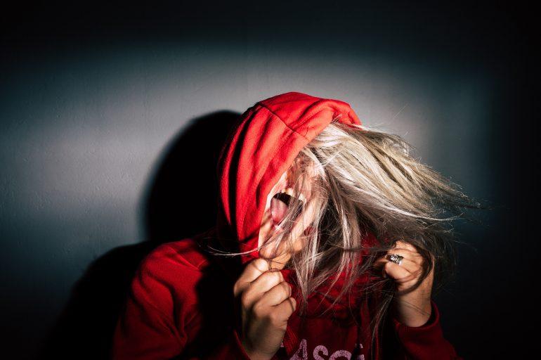 Foto van jonge vrouw met rode hoodie die het uitschreeuwt van frustratie
