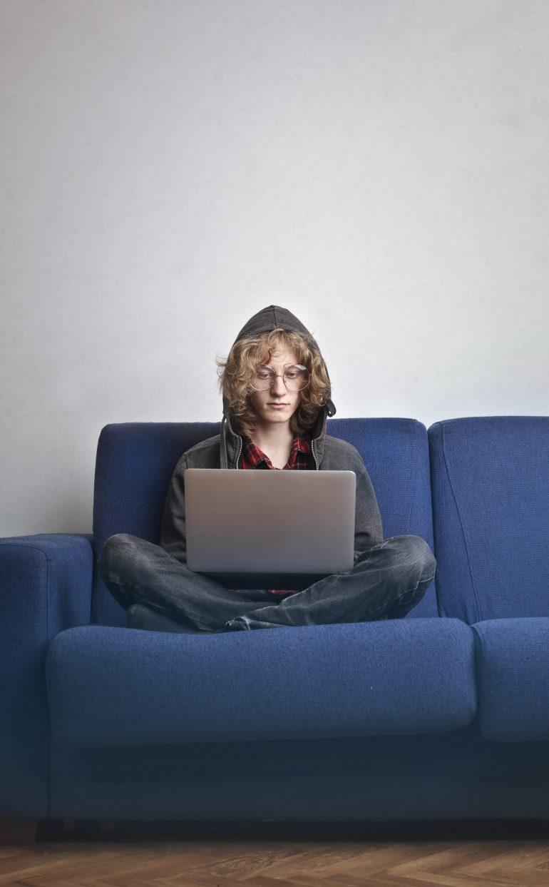 Foto van persoon met laptop, met hoodie op het hoofd, die geconcentreerd aan het werk is