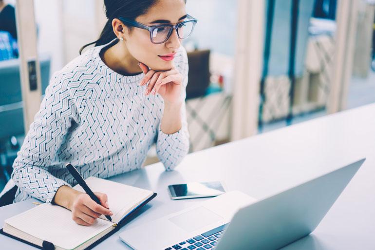 Vrouw maakt aantekeningen van webinar.