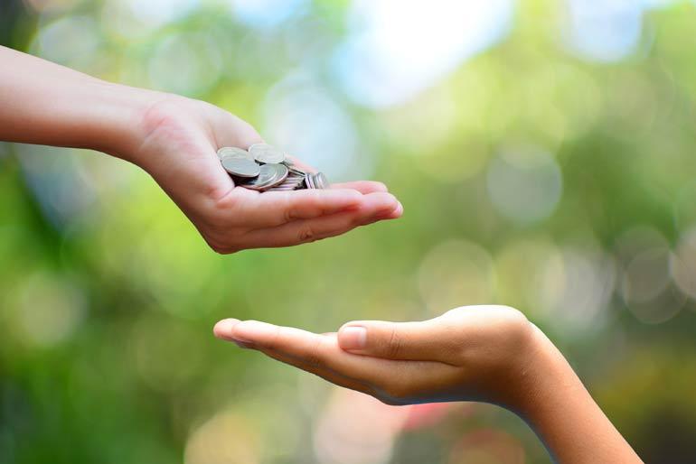 Hand geeft donatie geld aan andere hand.