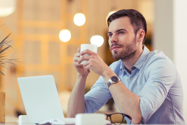 Man denkt na over blogs met kopje koffie.