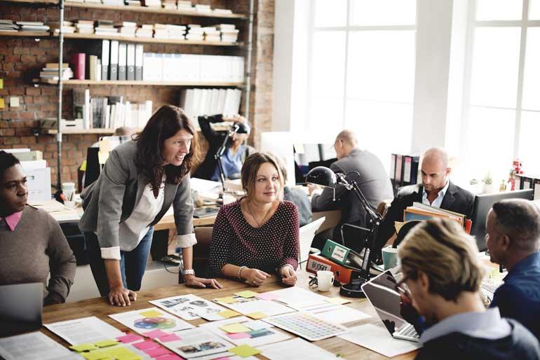 Een team overlegt aan tafel met concepten voor zich.