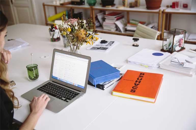 Vrouw met laptop en boeken.