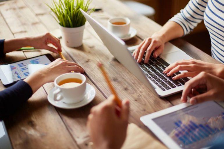 Mensen aan het werk op digitale werkplek met laptop en tablets.