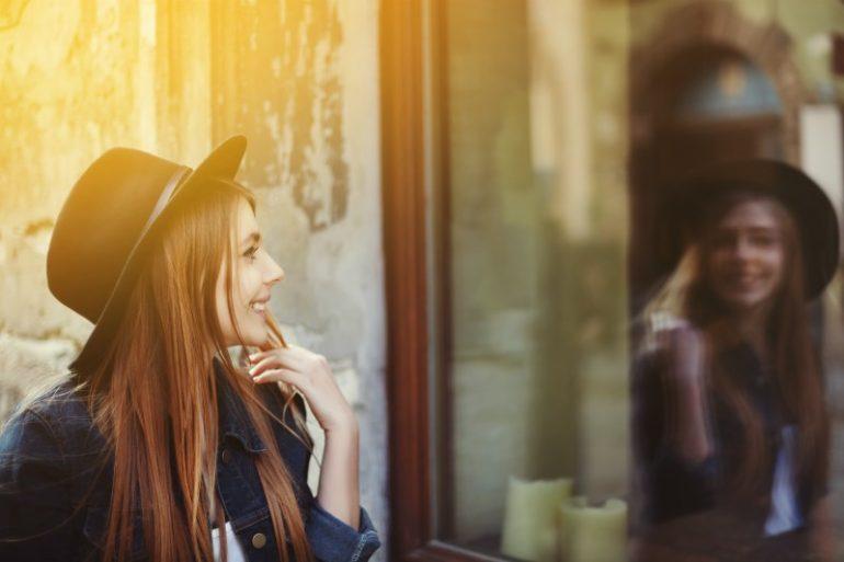meisje kijkt in spiegel.