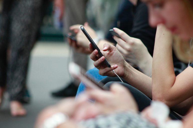 Mensen op hun telefoon, dat 'digitalisering' weergeeft.