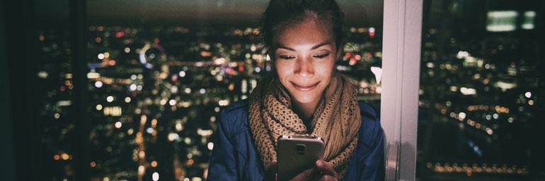 Vrouw op mobiel in het donker.