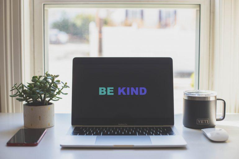 Tekst 'Be Kind' op een beeldscherm