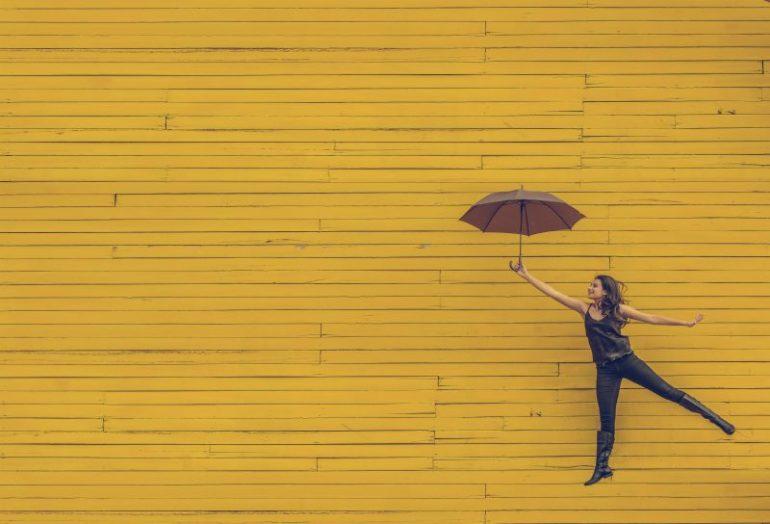 meisje met paraplu gele muur