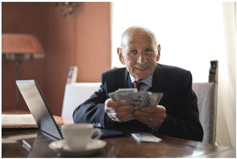 Oude man met geld in zijn handen. Bron: Pexels.