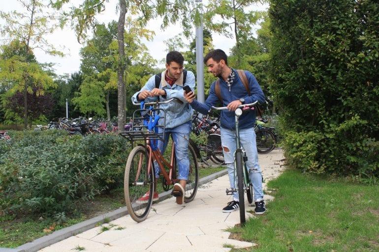 Twee studenten kijken naar hun mobiel op de fiets. Foto via Hogeschool Rotterdam.