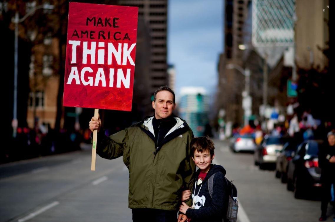 Man met een bord met de tekst 'Make America think again'.