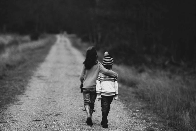Emotionele content, twee kinderen lopen samen over een pad
