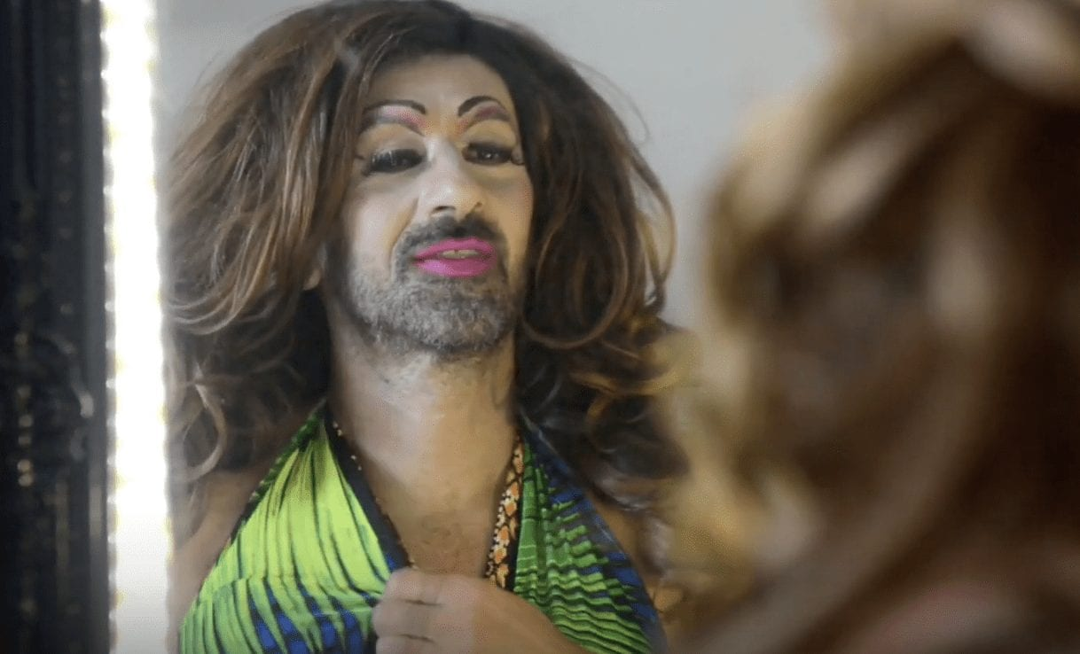 Een foto van iemand die zich schaalt achter de LHBT+ community.