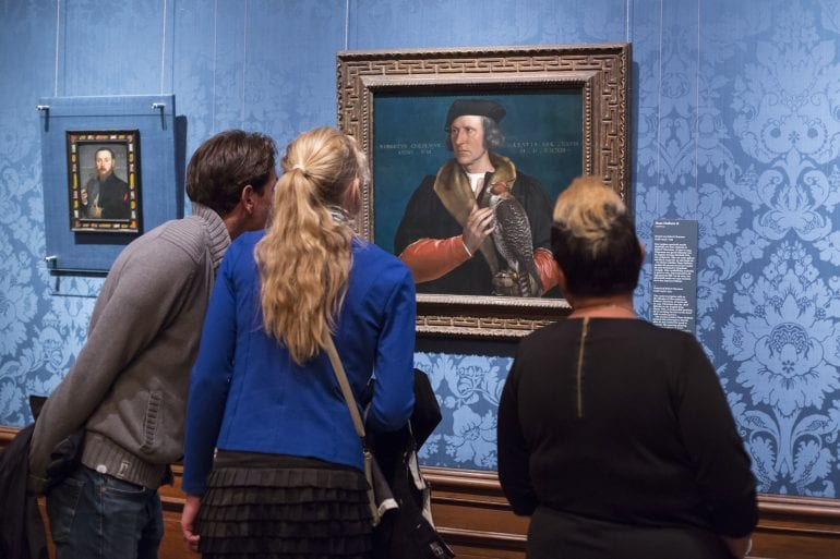 3 personen die naar een schilderij kijken.