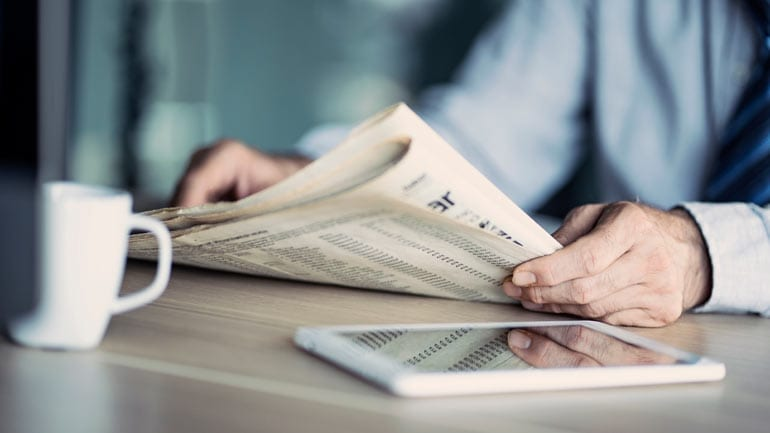 Man leest krant met kopje koffie.