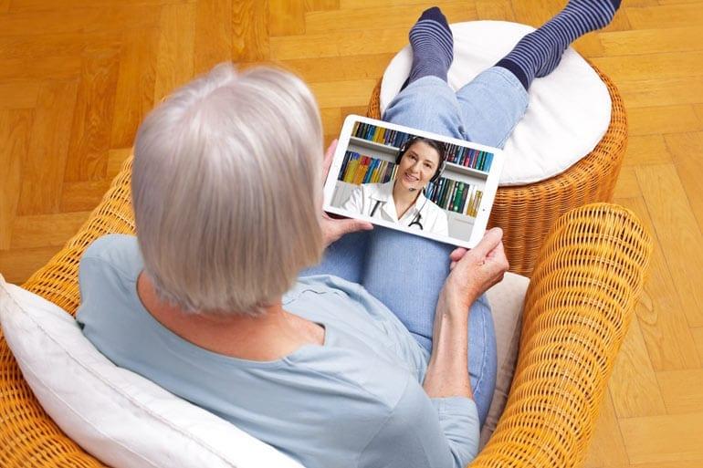 Oudere vrouw spreekt dokter via tablet.