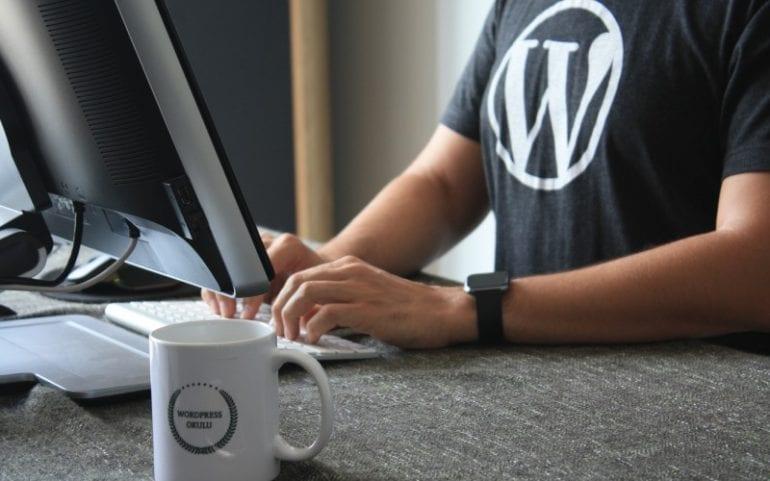 Bureau met monitor koffiemok en man in t-shirt met WordPress-logo en smartwatch