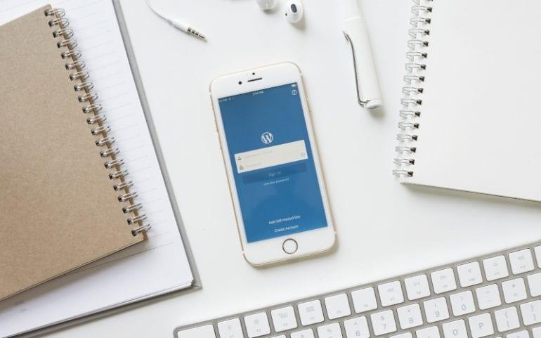 Bureau met notitieboekjes telefoon met WordPress-app toetsenbord oortjes en pen
