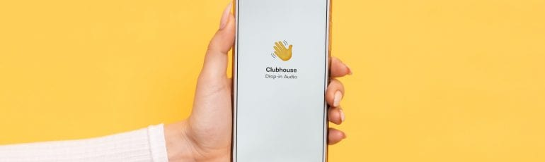 Iemand die een telefoon vasthoudt met de app Clubhouse in beeld.