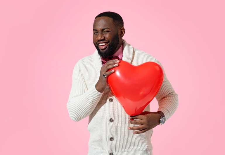 Man knipoogt en heeft groot rood hart in zijn handen.