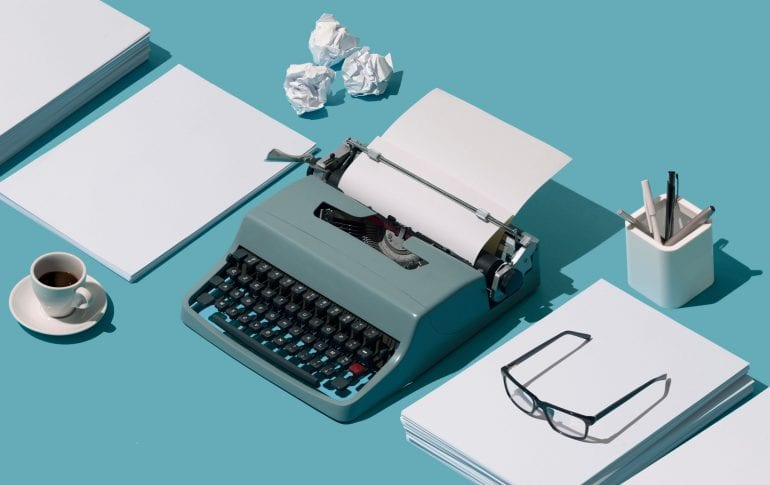 Lege en verkreukelde vellen papier en een typemachine