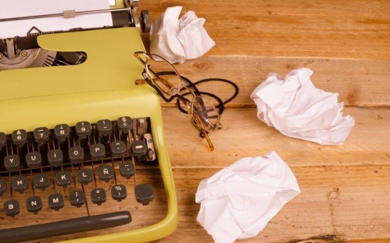 Typemachine op houten tafel met proppen papier en leesbril ernaast