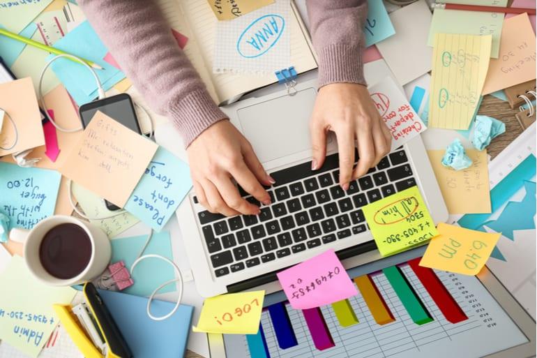 Vrouw werkt achter laptop en is overweldigd door alle taken.